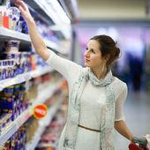 Belle jeune femme shopping pour les produits laitiers à une épicerie s — Photo