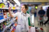 Mulher jovem e bonita de compras para produtos lácteos — Foto Stock