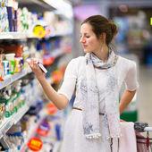Mooie jonge vrouw winkelen voor dagboek producten — Stockfoto