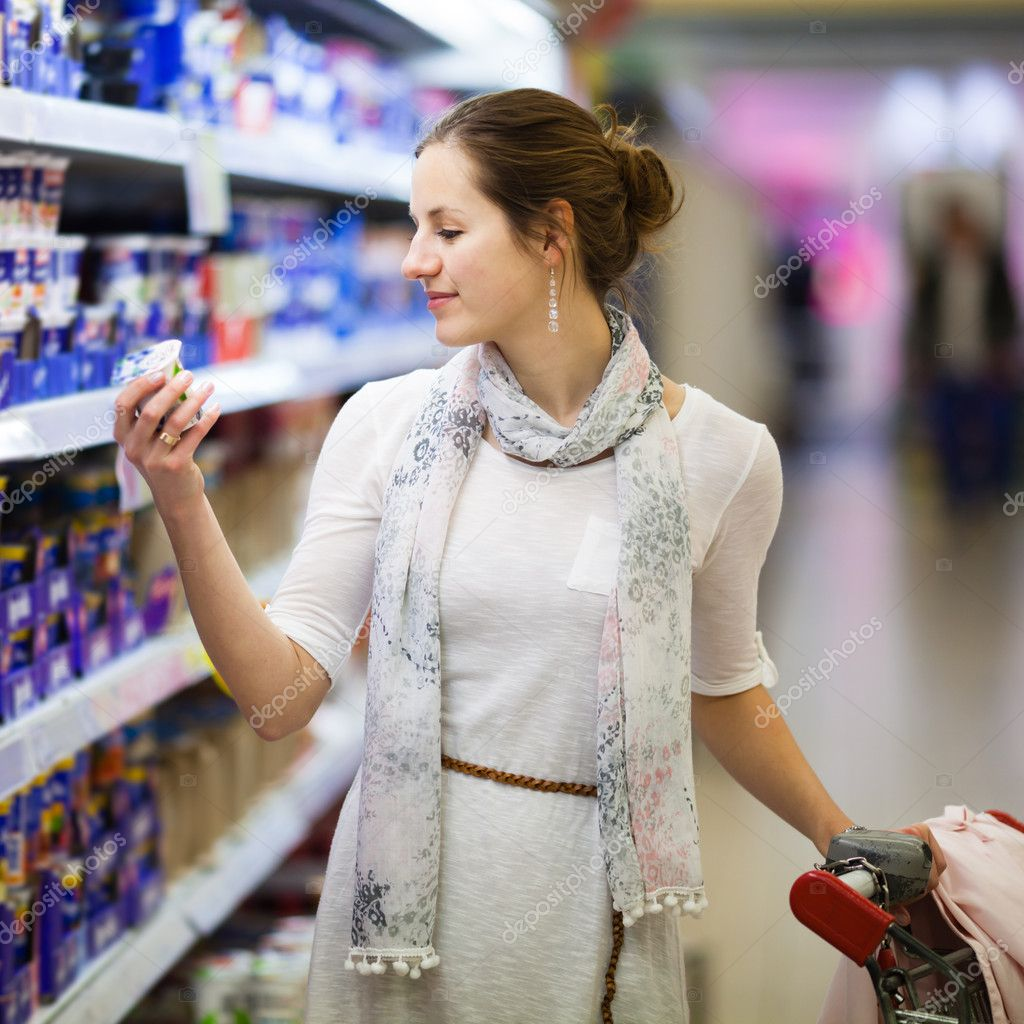 Beautiful young woman shopping for diary products at a grocery store/supermarket (color toned image) — Stock Photo #11302994