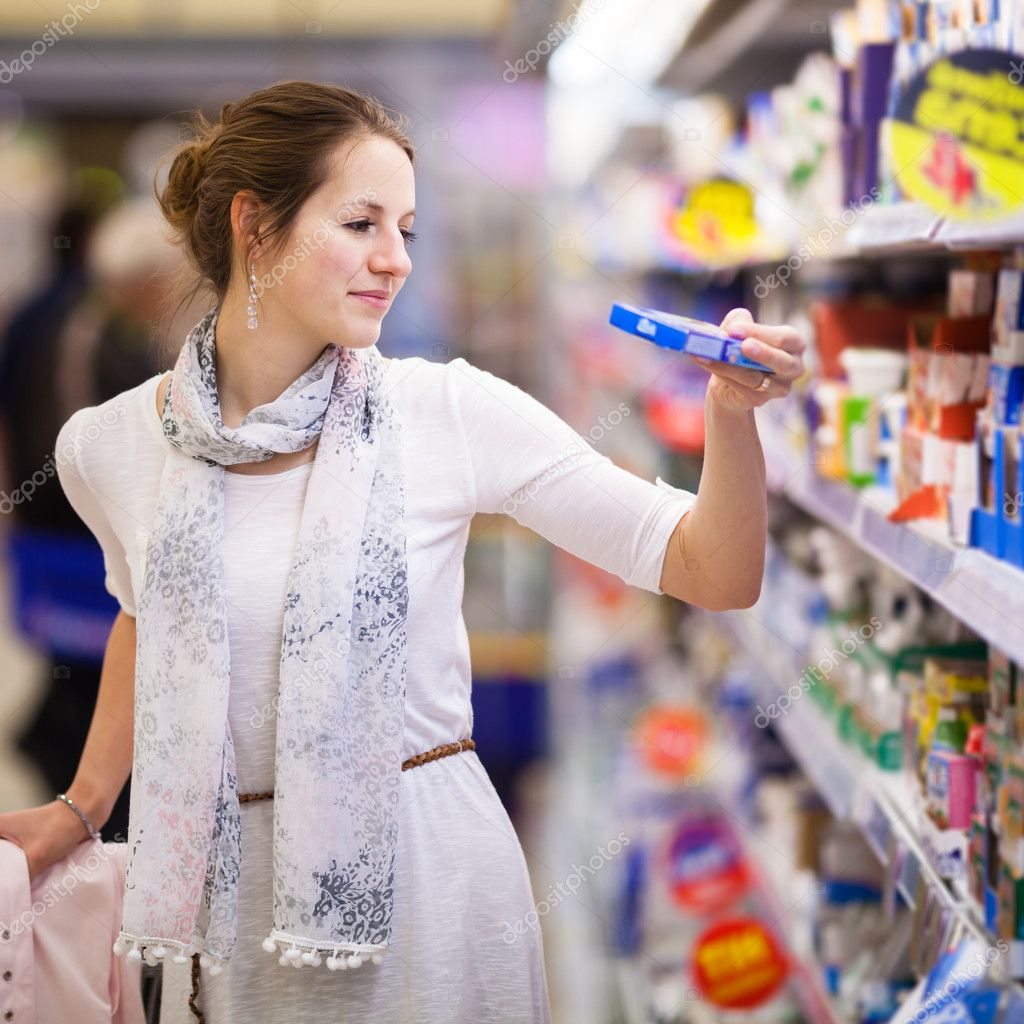 Beautiful young woman shopping for diary products at a grocery store/supermarket (color toned image) — Stock Photo #11303103