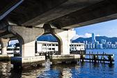 Horizonte de hong kong a lo largo de la orilla del mar bajo los puentes — Foto de Stock