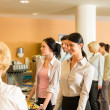 Cafeteria pay at cashier women in queue - Stock Photo