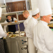 Group of cooks in professional kitchen - Stock Photo