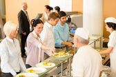 Office woman in canteen cook serve meals — Stock Photo
