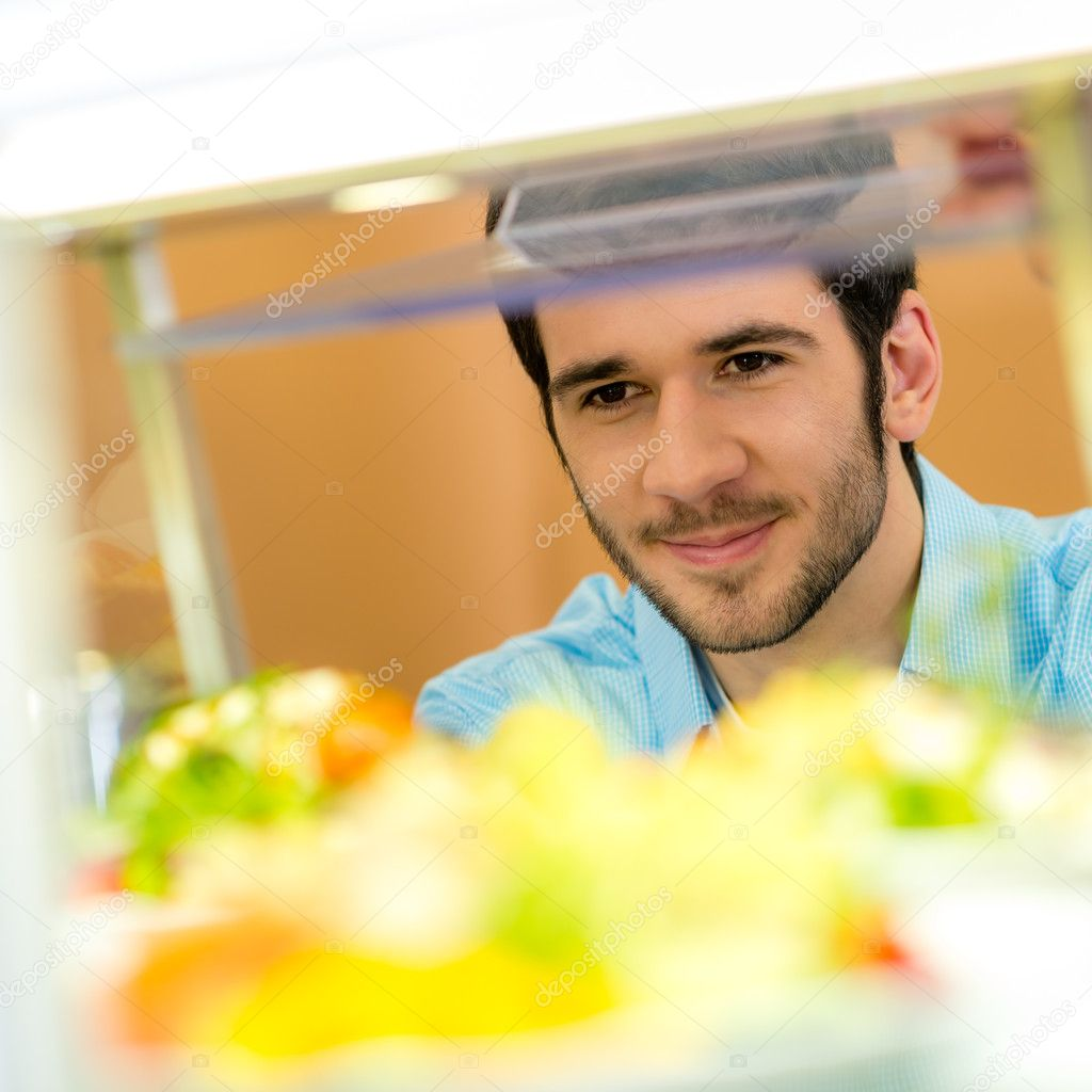 Cafeteria food display cabinet young man choose salad healthy lifestyle — Stock Photo #10745009