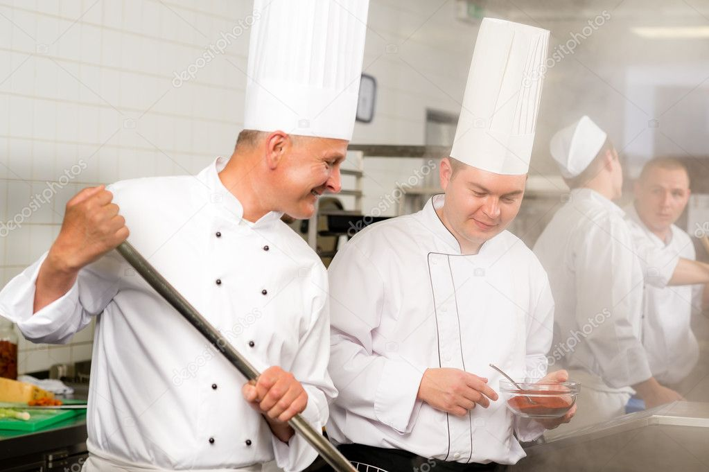 Two male cooks working in professional industrial kitchen prepare food — Stock Photo #10745413