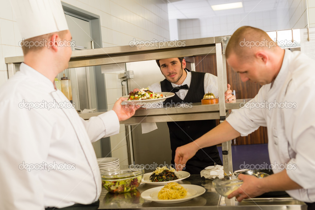 Professional kitchen cook prepare food service give meals to waiter — Stock Photo #10745503