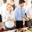 Business colleagues serve themselves at buffet — 图库照片