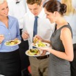 Business colleagues eat buffet appetizers — Zdjęcie stockowe