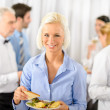 Smiling business woman during company lunch buffet - Stock Photo