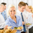 Smiling business woman during company lunch buffet - Zdjęcie stockowe