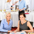 Two business women work during catering buffet — Stok fotoğraf
