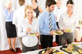 Business colleagues serve themselves at buffet — Стоковое фото