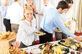 Business woman serve herself at buffet — Stock Photo