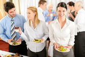 Business colleagues serve themselves at buffet — Stockfoto