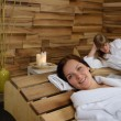 Happy woman at spa center lying down — Stock Photo