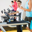 Stock Photo: Young fitness instructor womrunning at gym