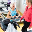 Royalty-Free Stock Photo: Young female friends chatting in fitness center