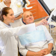 Man patient at dental consultation dentist surgery - Stock Photo