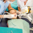 Dentist and assistant with child patient — Stock Photo