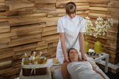 Woman enjoying neck massage at luxury spa — Zdjęcie stockowe