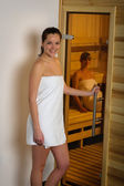 Women at sauna entering wrapped in towel — Stock Photo