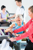 Young woman on fitness treadmill give instructions — Stock Photo