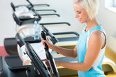 Fitness young woman on elliptical cross trainer — Stock Photo