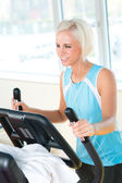 Young woman on fitness machine cardio exercise — Stock Photo