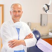 Mature dentist surgeon at office — Stok fotoğraf