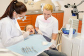 Dental assistant with dentist and little child — Stock Photo
