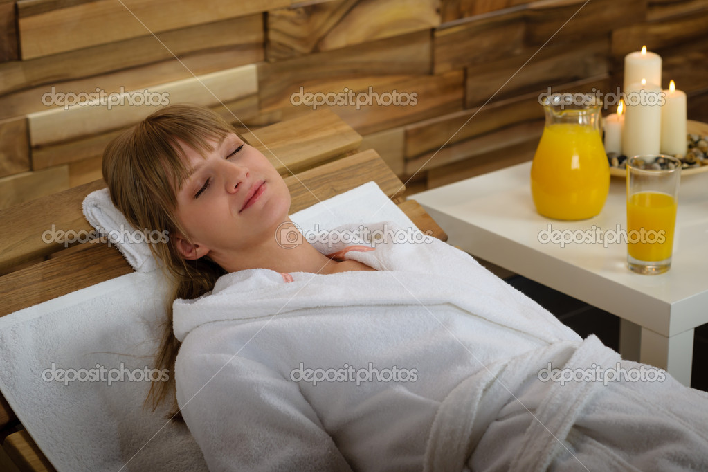 Young woman relaxing on wooden chair at luxury spa — Stock Photo #11137471