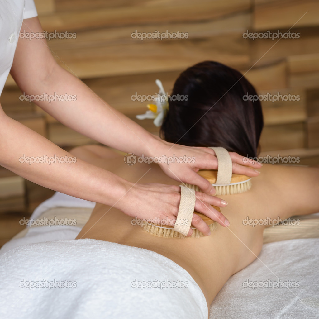 Beautiful brunette having wooden brush massage at luxury spa — Stock Photo #11137610