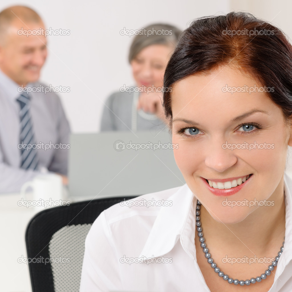 Smiling attractive businesswoman in office closeup with colleagues in background — Stock Photo #11375153