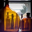 Stock Photo: Bottles standing on windowsill show rural view