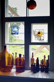 Bottles standing on windowsill in one line — Stock Photo
