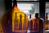 Bottles standing on windowsill show rural view — Stock Photo