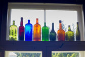Colored bottles standing on windowsill in line — Stock Photo