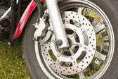 Bike chromed wheel on grassy background — Stock Photo