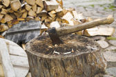 Rusty and used axe in wide stump — Stock Photo