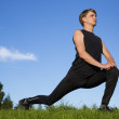 Stock Photo: Sportsmmaking exercise movements to stretch legs