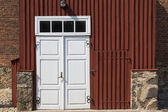 Wooden door in front of stony house — Stock Photo