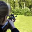 Woman targeting with hand weapon through sight — Stock Photo