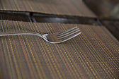 One chromed fork on kitche table — Stock Photo