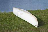 White canoe lay on green grass — Stock Photo