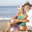 Senior couple sitting on beach relaxing — Stock Photo