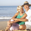 Senior couple sitting on beach relaxing - Stock Photo