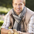 Young man posing with potatoes in garden — Stock Photo