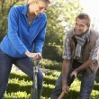 Young couple working in garden - Stock fotografie